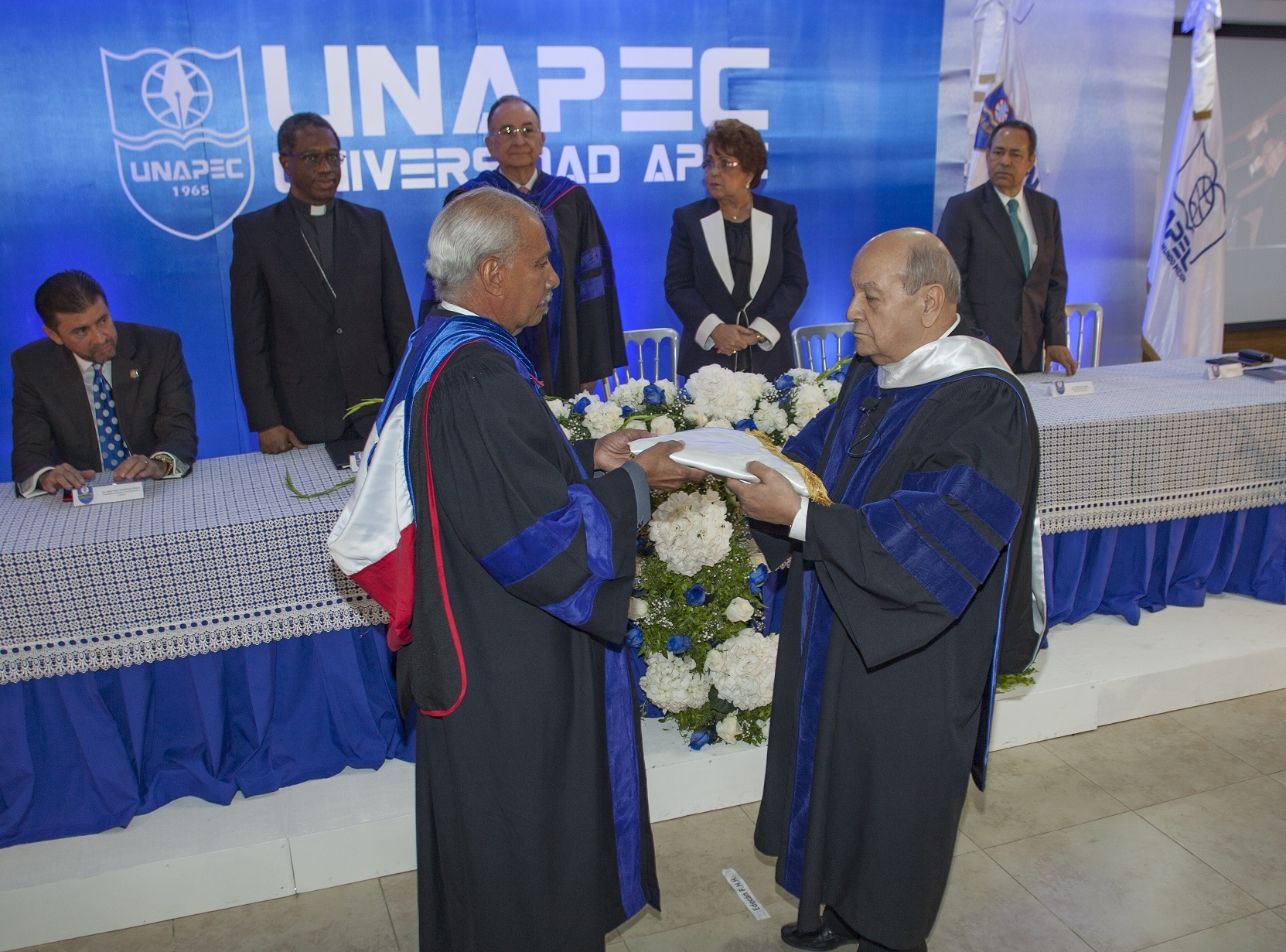 Lic. Francisco D Oleo, Vicerrector Acádemico, entrega Bandera de UNAPEC al nuevo Rector.
